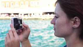 Young woman takes the photo a lighthouse in a European city uses smartphone stock video