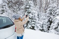 Young woman takes photo of snow-covered winter forest. Stock Photo