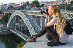 Young woman takes photographs of Dom Luis I bridge, Porto Royalty Free Stock Images