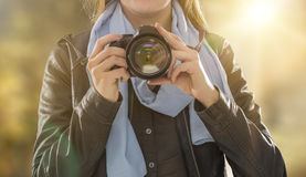 Portrait of a photographer covering her face with camera. Royalty Free Stock Photo