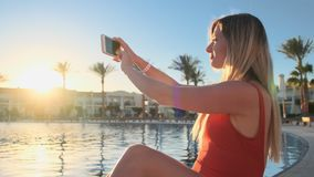 Young woman takes pictures of sunset with phone while relaxing near the swimming pool at luxury villa. Close up of stock footage