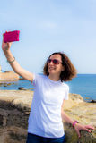 Young woman takes selfie in front to the sea with a smartphone Royalty Free Stock Photos