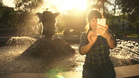 A young woman takes a selfie on a phone near a fountain in a public park. A young woman takes photos using a smart phone camera at the fountain in summer at stock footage