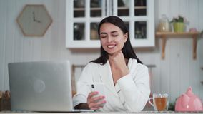 Young woman takes selfie on phone, uses smartphone and laptop for work at home. Smiling girl posing on photo camera stock footage