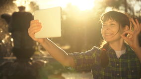 A young woman takes a selfie on a tablet near a fountain in a public park. A young woman in a plaid shirt shows an ok sign, making a video call using the stock footage