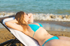 Young woman takes sunbathing on the beach Stock Images