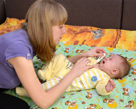 The young woman takes temperature to the sick crying baby the electronic thermometer Royalty Free Stock Photos