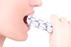 Young woman taking blister of pills between her lips isolated on. White background Royalty Free Stock Images