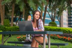 Young woman taking a break to relax from work on the laptop in park while holding cup of coffee in one hand with her Stock Photos