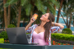 Young woman taking a break to relax from work on the laptop in park while holding cup of coffee in one hand with her Royalty Free Stock Image