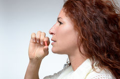 Young woman taking a capsule Royalty Free Stock Image