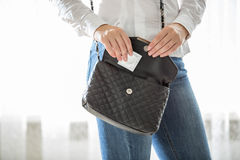 Young woman taking condom out of handbag Stock Image
