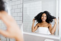 Young woman taking deciding on a hairstyle. In front of a mirror Stock Photo