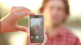 Young woman taking funny pictures of man with phone. View of a woman's hand holding a mobile phone and taking pictures man at sunset stock video