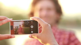Young woman taking funny pictures of man with phone. View of a woman's hand holding a mobile phone and taking pictures man at sunset stock video footage