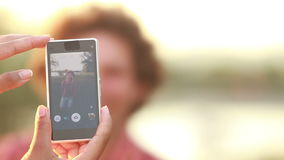 Young woman taking funny pictures of man with phone. View of a woman's hand holding a mobile phone and taking pictures man at sunset stock footage