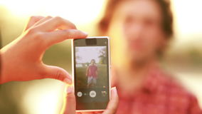 Young woman taking funny pictures of man with phone stock footage