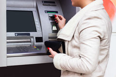Young woman taking money from ATM Royalty Free Stock Images