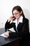 Young woman taking notes while speaking on phone. Business woman takes notes while speaking on phone Royalty Free Stock Photo