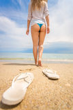 Young woman taking off flip flops and and walking on the beach Stock Photos