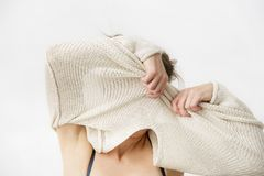 Young woman is taking off her sweater, covering her face. stock image