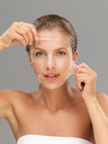Young woman taking off peeling mask Royalty Free Stock Photo