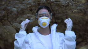 Young woman taking off protective mask breathing free in forest, climate change