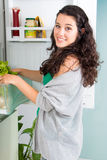 Young woman taking out a lettuce from refrigerator Stock Image