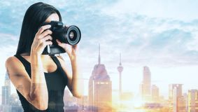 Young woman taking photo. Attractive young woman taking photo with professional camera on sunny New York city background. Hobby and leisure concept. Double stock photography