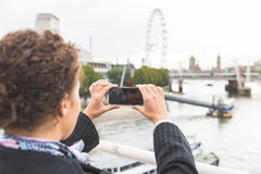 Young woman taking photo of Big Ben in London with her smart pho. Ne. She is a mixed race woman on her late twenties, with light dark skin and curly hair Stock Images