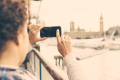 Young woman taking photo of Big Ben in London with her smart pho. Ne. She is a mixed race woman on her late twenties, with light dark skin and curly hair Royalty Free Stock Images