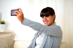 Young woman taking a photo with cellphone at home Stock Photos