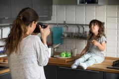 Young woman taking photo cute little girl in kitchen royalty free stock photo