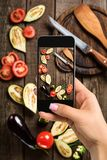A young woman taking photo of food on smartphone, photographing meal with mobile camera Royalty Free Stock Images