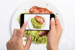 A young woman taking photo of food on smartphone, photographing meal with mobile camera Stock Photos