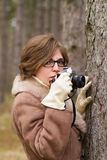 Young woman taking photo in the forest Stock Image