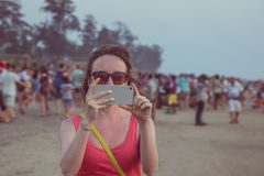 Young woman are taking photo on her mobile on Arambol beach at s Royalty Free Stock Photography