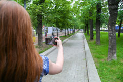 Young woman taking a photo with her phone. In the park Stock Image