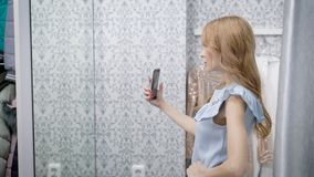 Young woman is taking photo of her reflection in a mirror of fitting room of clothing store, using smartphone. Young woman is taking photo of her reflection in a stock video footage