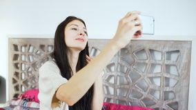Young woman taking photo or making selfie in her bedroom stock footage