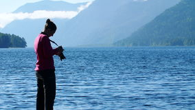 Young woman taking photo of mountain. woman photographer taking photo at the lake. stock footage