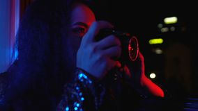 Young woman taking photo of night city illumination by camera, creative hobby. Stock footage stock footage