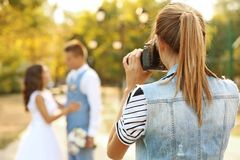 Free Young Woman Taking Photo Of Wedding Couple In Park Royalty Free Stock Image - 120344726