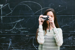 Young woman taking a photo with an old camera. Stock Photography