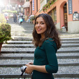 Young woman taking photo in Salita Serbelloni picturesque small town street view in Bellagio, Lake Como, Italy.  Royalty Free Stock Images