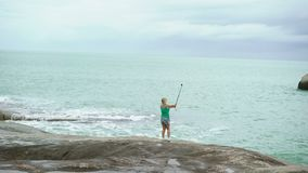 Young woman taking photo with selfie stick near sea. On rocks stock footage