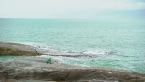 Young woman taking photo with selfie stick near sea. On rocks stock video footage