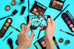 Young woman taking photo to cosmetics with cell phone or smartphone digital camera for post to sell online on the Stock Photos