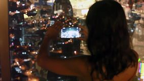 Young woman taking photo top of a building with smart phone at the top of a skyscraper in Penang at night with a blur stock video footage