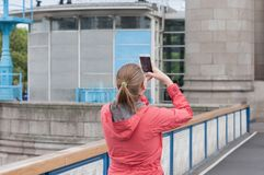 Young woman is taking photo of Tower Bridge by her phone in Lond. On Stock Image